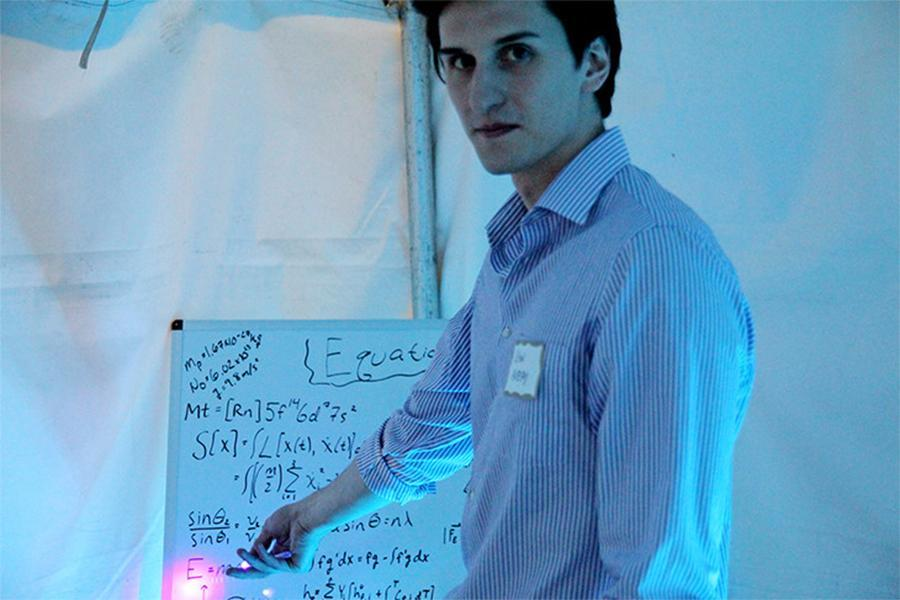 """Sean Avery, who is majoring in electrical engineering, grants tours at the STEM-based escape room themed """"hidden figures"""" at the"""